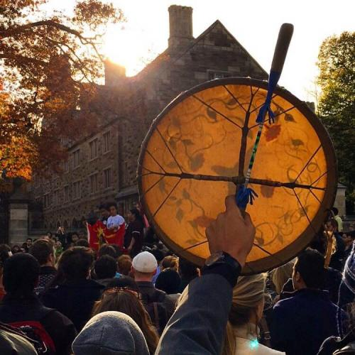 Professor Ned Blackhawk holding a hand drum in salute of the Yale Blue Feather Drum Group as they performed during the March of Resilience. [Photo credit: Tyler Rogers]